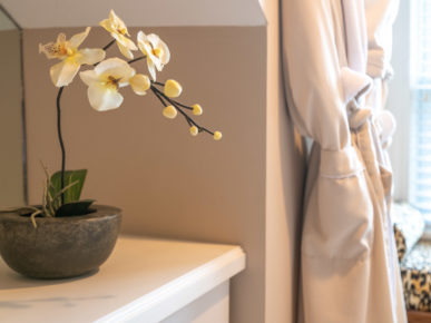 An orchid rests next to a luxurious robe